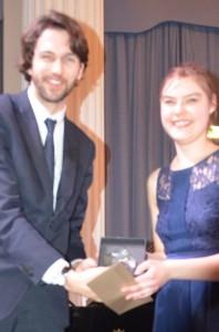 Rebecca McNaughtreceives the Hewitt-Jones Trophy from Thomas Hewitt-Jones