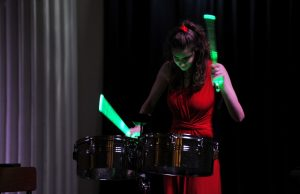 Darcy Beck playing timbales using light sticks